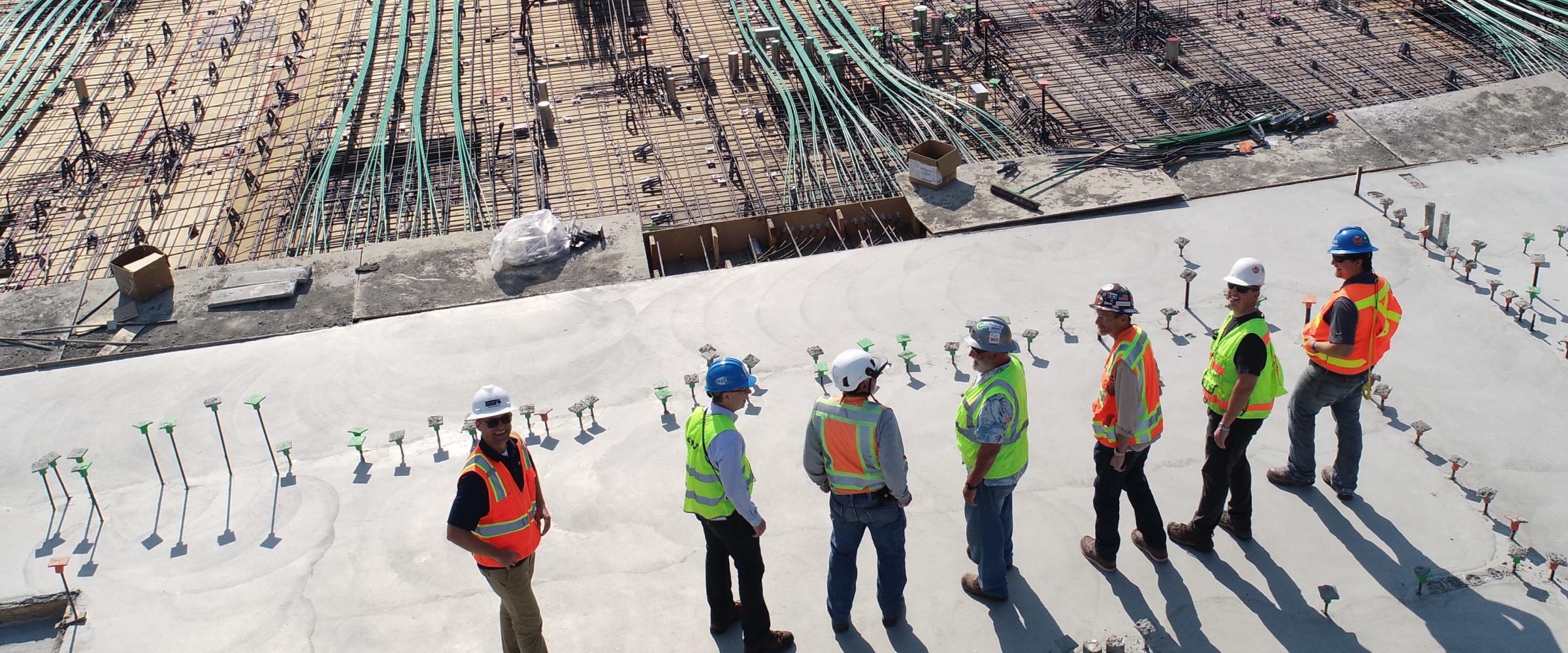 Men in hard hats stand overlooking construction site