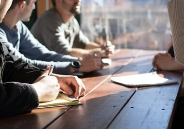 employees hands at table, coworkers meeting