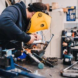 man in mask welds in a workshop